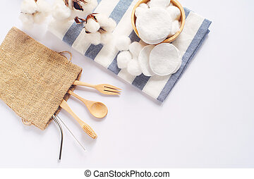 Flat lay of sustainable products, wooden spoon, stainless straw and natural cotton on white background and copy space, eco friendly and zero waste concept