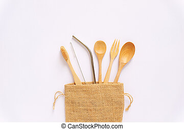 Flat lay of sustainable products, wooden spoon, stainless straw in natural sack bag on white background, eco friendly and zero waste concept