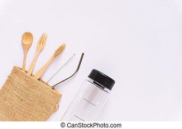 Flat lay of sustainable products, wooden spoon, stainless straw in sack bag with bottle on white background and copy space, eco friendly and zero waste concept