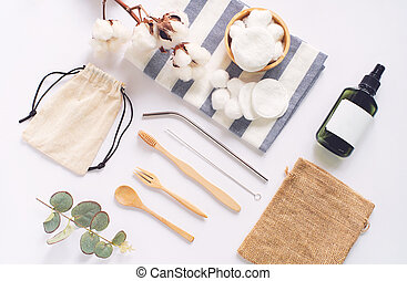Flat lay of sustainable products, wooden spoon, stainless straw, organic cosmetic and natural cotton on white background, eco friendly and zero waste concept