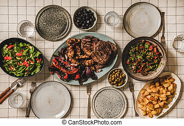 Flat-lay of table with grilled meat, chicken, vegetables, salads, potato