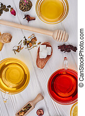 Flat lay of tea composition on white wooden background.