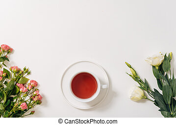 Flat lay of tea cup standing between flowers - Fragrant...