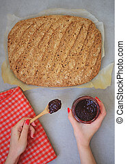 Flat lay of woman hands holding jar of Raspberry jam and freshly baked bread on table
