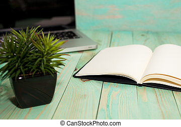 Flat lay of workspace desk with laptop smartphone blank notebook and green plant