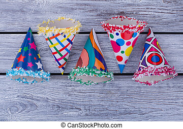 Flat lay party hats on wooden background.