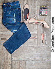 Flat lay photo of girl's jeans and accessories on wooden...