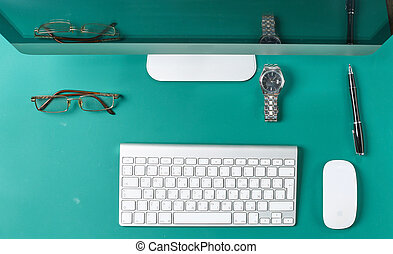Flat lay photo of office desk with keyboard, notebook, tablet, smartphone, eyeglasses