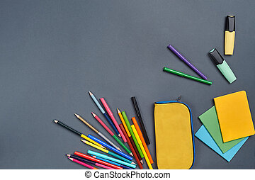 Flat lay photo of workspace desk with school accessories or office supplies on gray background.