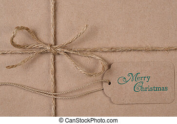 Flat lay plain brown paper wrapped Christmas Present with twine and tag