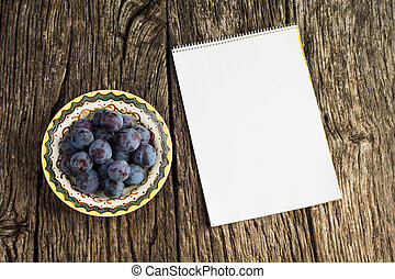 Flat lay. Ripe plums on old vintage plate on dark rustic wooden background with empty notebook.