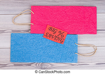Flat lay shopping bags on wooden background.