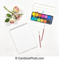 Flat lay sketchbook watercolor brushes paper rose flowers