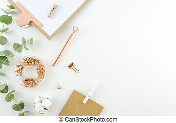 Flat lay, Top view office supplies table desk. Feminine desk workspace frame with green leaves eucalyptus, clipboard and cotton on white background. ideas, notes or plan writing concept. Hero header