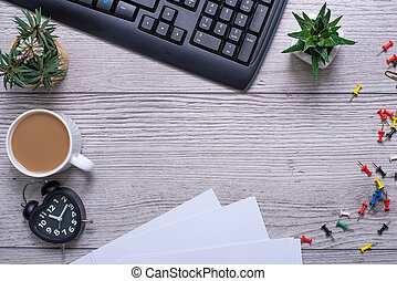 Flat lay, top view office table desk. Workspace with blank clip board, keyboard, office supplies and alarm clock on wooden background. office products and stationery framed.