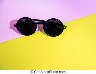 flat lay top view sunglasses on two tone background, pink and yellow