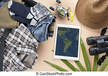 Flat lay travelling set with spinning of fishing tools, binoculars, hat, man cloths and gadget with map on pastel background. travel concept - Image