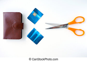 Flat lay view of a  pair of scissors with a cut credit cared and a wallet