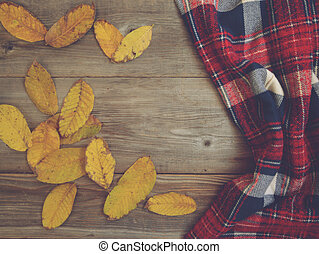 Flat lay view of autumn leaves and tartan textured scarf on wooden background