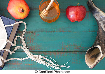 Flat lay view of Torah book, tallit, pomganet, honey jar and red apple on a turquoise background. Rosh Hashanah Jewish new year holiday concept. Copy space