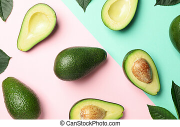 Flat lay with avocado and leaves on two tone background, top view
