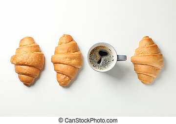 Flat lay with croissants and cup of coffee on white background, top view