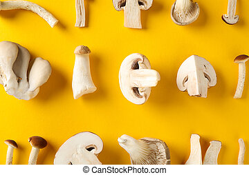 Flat lay with different mushrooms on yellow background, close up
