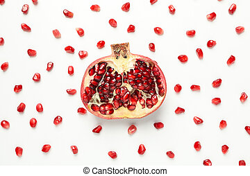 Flat lay with half of pomegranate and seeds on white background