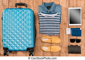 Flat lay with luggage, male clothes, accessories and digital tablet on wooden floor. Ready for travel concept
