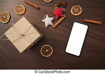 flat lay with smarthone and christmas decorations on walnut table, top view