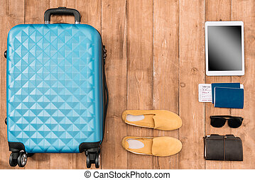 Flat lay with travel accessories on the floor. Baggage, shoes, passports, sunglasses, wallet, digital tablet.