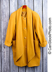 Flat lay yellow coat, top view.