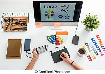 Flat layout of hands of web designer with stylus over screen of graphics tablet