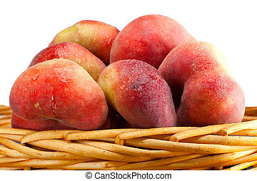 flat peaches in water drops in a basket