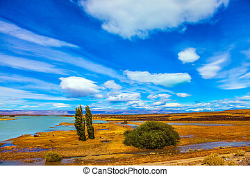 Flat plain with shallow lakes and yellowed grass. Patagonian Pampas. Concept of active and exotic tourism