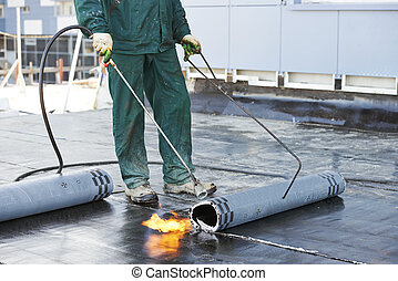 Roofer installing Roofing felt with heating and melting of bitumen roll by torch on flame during roof repair