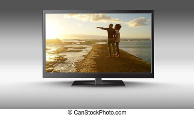 Flat screen TV with a couple at the beach on its screen