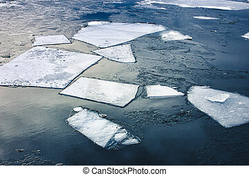 Flat slabs of ice floating on blue clear water