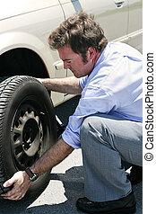 Flat Tire - Dirty Job - A businessman changing a flat tire...