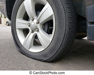Flat tire in parking lot of apartment building.
