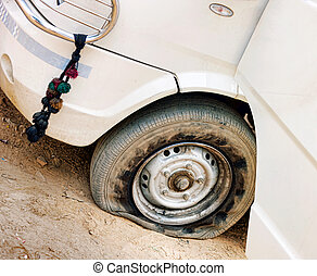 Flat tire of white car