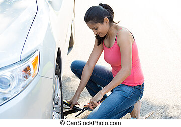 Flat tire repair - Closeup portrait, young woman in pink...