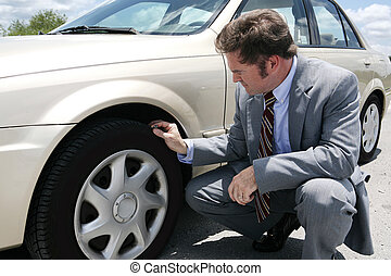 Flat Tire with Screw - A businessman on the road with a ...