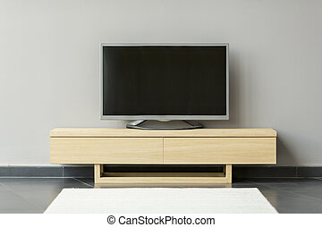 Flat-TV standing on the commode in the room