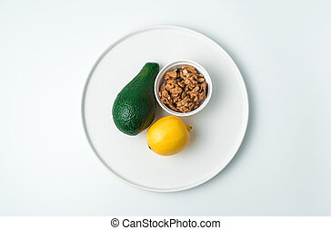 Flat white plate with avocado and lemon and walnuts on a white background.