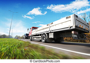 Flatbed truck and cars in motion on the countryside road against sky with clouds