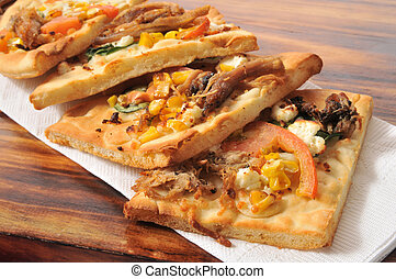 Gourmet flatbread appetizers with shredded beef, tomato, feta cheese and corn