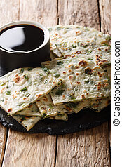 Flatbread fried onion pancakes served with sauce close-up on...
