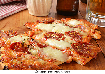 Hearth baked garlic and pepperoni flatbread pizza with a mug of beer