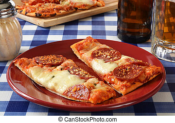 Flatbread garlic and pepperoni pizza on a picnic table with beer